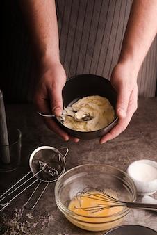 Wysoki kąt kucharz pokazuje miksturę w misce