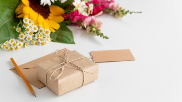 Wysoki kąt kwiatów z prezentem i przywieszką