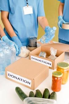 Wysoki kąt ludzi przygotowujących pudełka z darowiznami żywności