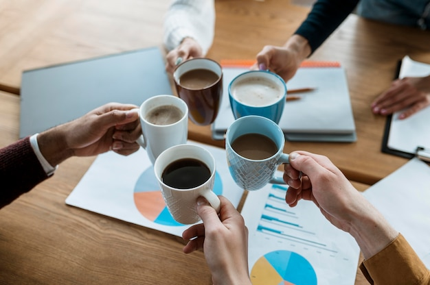 Wysoki kąt ludzi wiwatujących z kubkami kawy podczas spotkania w biurze