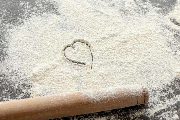 Wysoki kąt mąki i drewniany wałek do ciasta