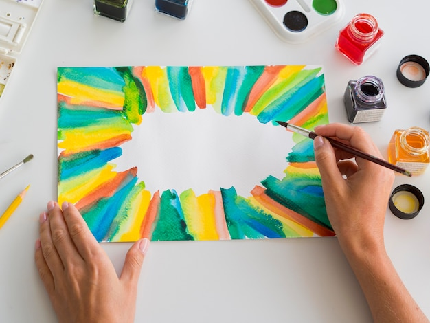 Wysoki kąt malowania artysty akwarelą i pędzlem