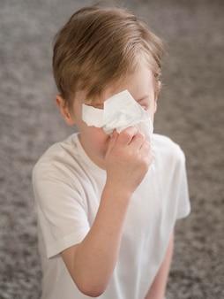 Wysoki kąt mały chłopiec dmuchanie nosa