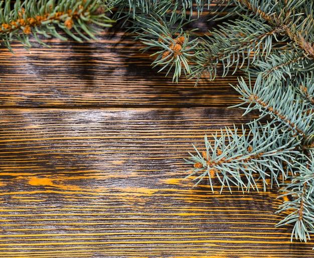 Wysoki kąt martwa natura z gałęzi sosny na drewnianym stole z rustykalnym wzorem ziarna - świąteczne tło z miejscem na kopię