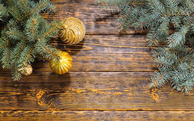 Wysoki kąt martwa natura z gałęzi sosny ozdobione złotymi kulkami na drewnianym stole z rustykalnym wzorem ziarna - świąteczne tło boże narodzenie z miejscem na kopię na tekst