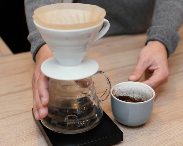 Wysoki kąt męski barista trzymający filiżankę kawy i filtr