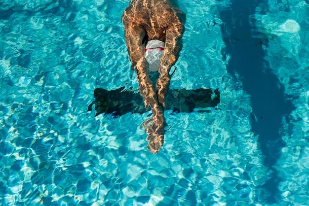 Wysoki kąt męskiego pływaka w basenie z wodą