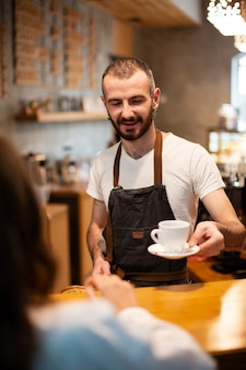 Wysoki kąt mężczyzna barista serwująca kawę