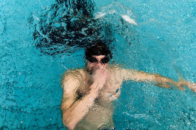 Wysoki kąt mężczyzna trzyma oddech pod wodą