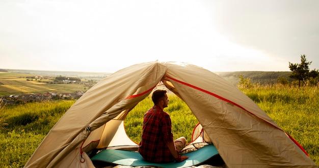Wysoki kąt mężczyzna w namiocie kempingowym