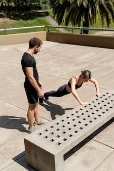 Wysoki kąt mężczyzny i kobiety robienie pompek na zewnątrz