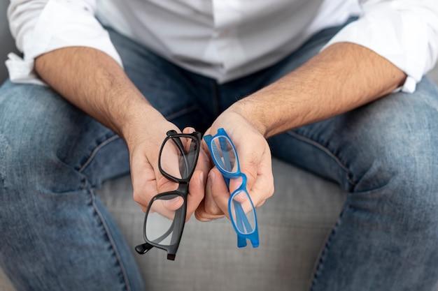 Wysoki kąt mężczyzny siedzącego i trzymającego w rękach dwie pary okularów