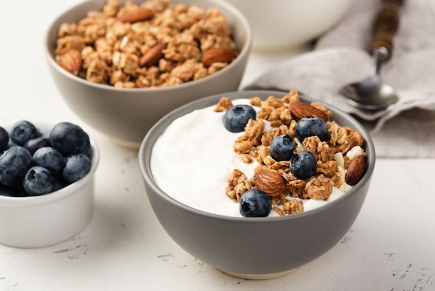 Wysoki kąt misek płatków śniadaniowych z jagodami i jogurtem