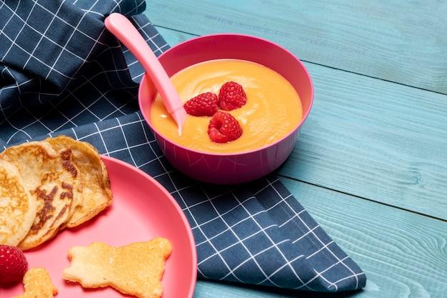 Wysoki kąt miski z jedzeniem dla niemowląt i malinami