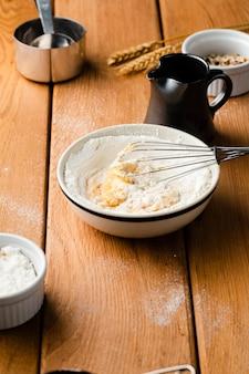 Wysoki kąt miski z trzepaczką na drewnianym stole