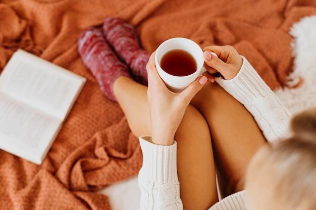 Wysoki kąt młoda kobieta trzyma filiżankę herbaty