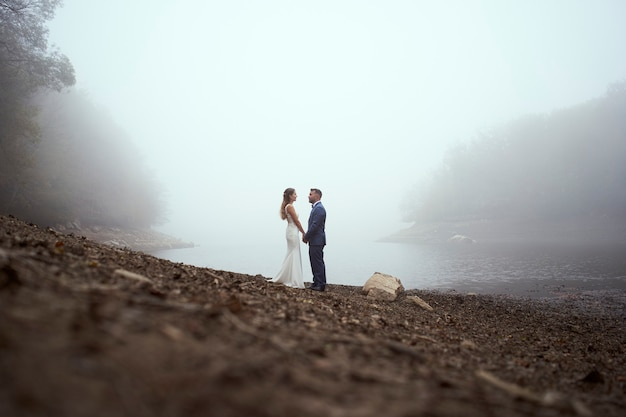 Wysoki kąt młoda para w sukniach ślubnych, trzymając się za ręce i patrząc na siebie