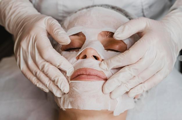Wysoki kąt młodej pięknej kobiety podczas zabiegu maski na skórę