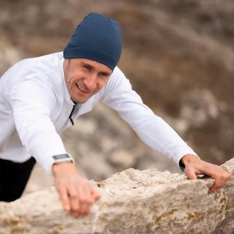 Wysoki kąt młody człowiek wspinaczka skały w przyrodzie