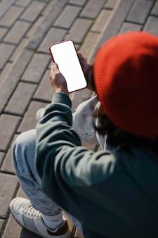Wysoki kąt nastolatek na zewnątrz za pomocą smartfona
