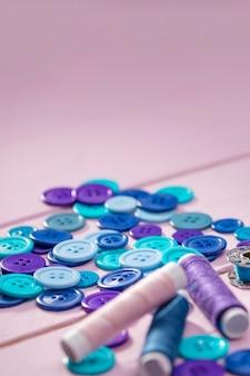 Wysoki kąt niebieskich przycisków z miejsca kopiowania i szpule nici