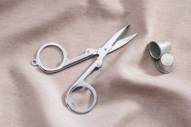 Wysoki kąt nożyczek z naparstkami na tkaninie