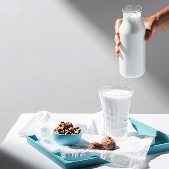 Wysoki kąt osoby nalewającej mleko do szklanki z orzechami włoskimi na tacy