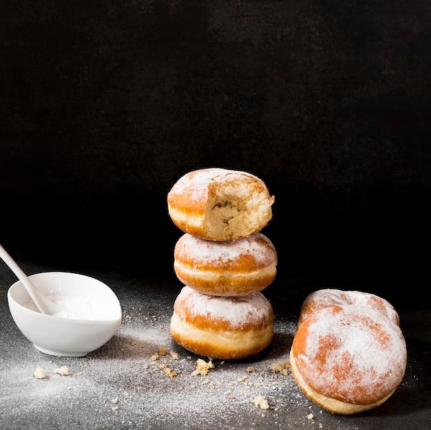 Wysoki kąt pączków ze znakiem ugryzienia i cukrem pudrem