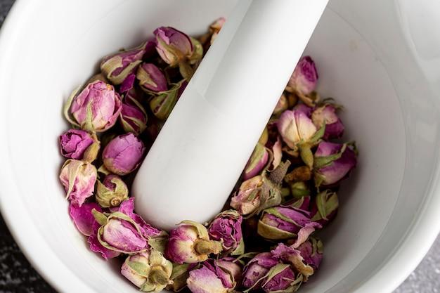 Wysoki kąt pąków róży w moździerzu z tłuczkiem