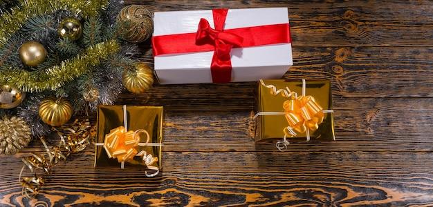 Wysoki kąt panoramiczny widok prezentów świątecznych na rustykalnym drewnianym stole obok wiecznie zielonych gałęzi sosny ozdobionych złotymi kulami i girlandą ze świecidełek - świąteczna martwa natura z miejscem na kopię