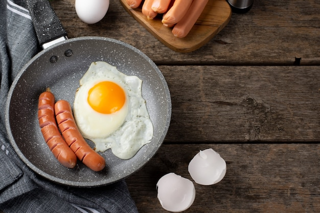 Wysoki kąt patelni z jajkiem i kiełbaskami na śniadanie