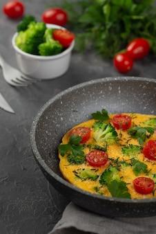 Wysoki kąt patelni z omletem śniadaniowym i pomidorami