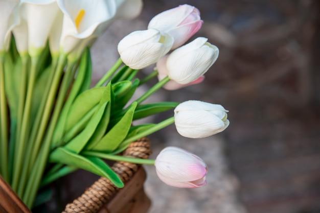Wysoki kąt pięknych tulipanów w koszyku
