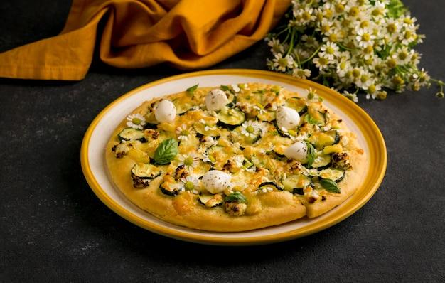 Wysoki kąt pizzy na talerzu z kwiatami rumianku