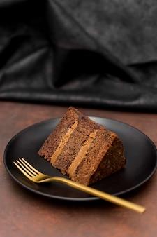 Wysoki kąt plasterek ciasta na talerzu ze złotym widelcem
