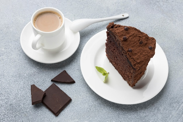 Wysoki kąt plasterek ciasto czekoladowe na talerzu z kawą