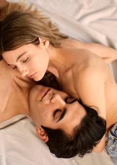 Wysoki kąt pociągającej kobiety i mężczyzny bez koszuli w łóżku