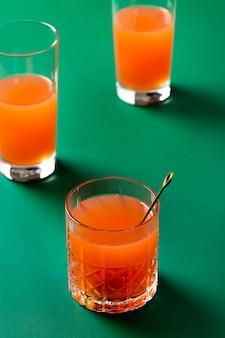 Wysoki kąt pomarańczowe napoje na zielonym tle
