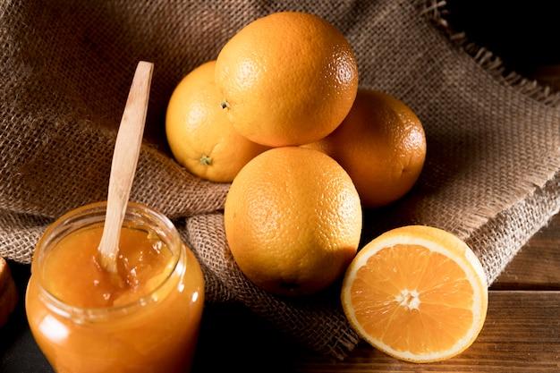 Wysoki kąt pomarańczowej marmolady w słoiku z owocami