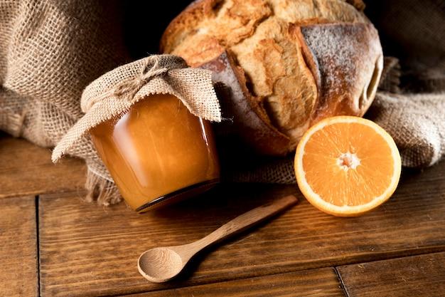 Wysoki kąt pomarańczowy słoik marmolady z chlebem