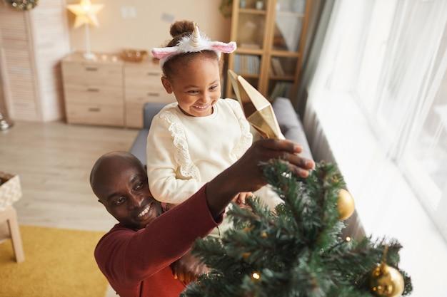 Wysoki kąt portret cute african-american girl dekorowanie choinki z kochającym ojcem, ciesząc się sezonem wakacyjnym w domu