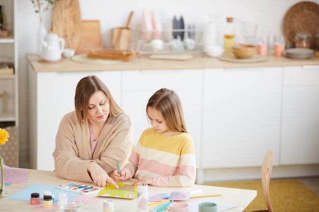 Wysoki kąt portret dojrzałej matki pomagającej ślicznej córce w projektach artystycznych i rzemieślniczych we wnętrzu domu, kopia przestrzeń
