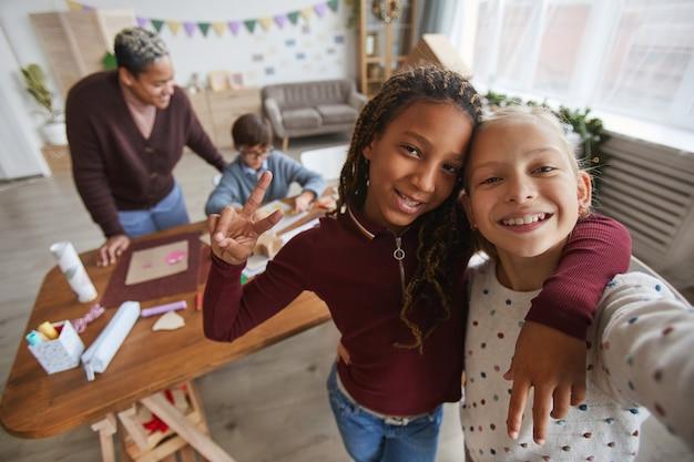 Wysoki kąt portret dwóch nastoletnich dziewcząt robienia zdjęć selfie podczas zajęć plastycznych w szkole z nauczycielem w tle, kopia przestrzeń