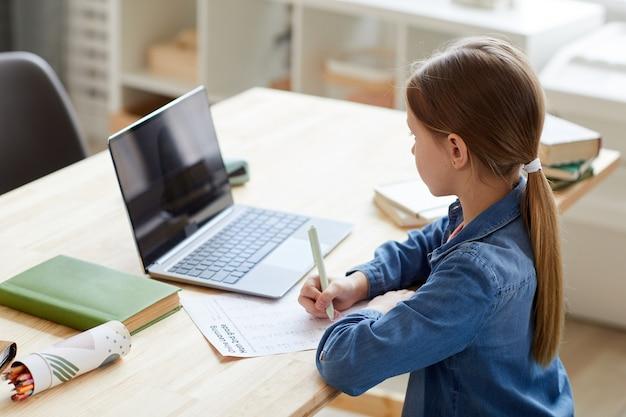 Wysoki kąt portret dziewczynki za pomocą laptopa podczas zajęć online z korepetytorem lub nauczycielem podczas nauki w domu siedzącej przy biurku w przytulnym wnętrzu, miejsce na kopię