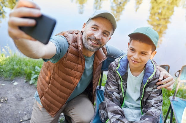 Wysoki kąt portret kochającego ojca i syna, którzy robią selfie na smartfonie, ciesząc się razem na kempingu