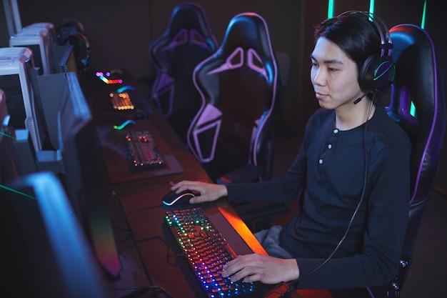 Wysoki kąt portret młodego mężczyzny azjatyckich, grając w gry wideo w fotelu sportowym cyber, kopia przestrzeń