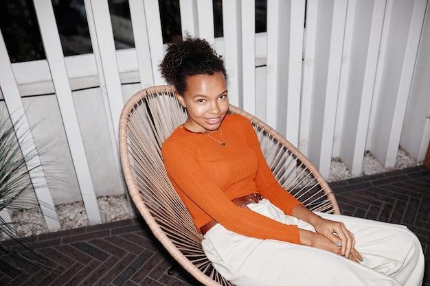 Wysoki kąt portret młodej afroamerykańskiej dziewczyny relaksującej się w fotelu na imprezie, nakręcony z lampą błyskową