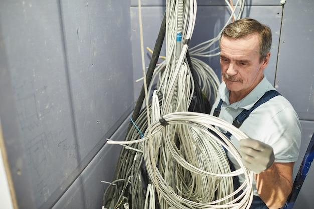 Wysoki kąt portret starszego elektryka łączącego kable w szafie przewodów podczas remontu domu, miejsce na kopię