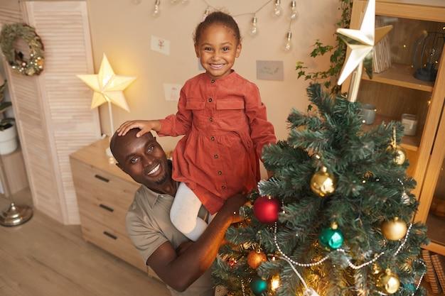Wysoki kąt portret szczęśliwy african-american girl dekorowanie choinki z kochającym ojcem trzymając ją, ciesząc się sezonem wakacyjnym w domu