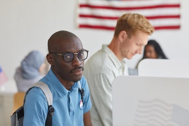 Wysoki kąt portret współczesnego człowieka afroamerykanów odwracając, stojąc w kabinie do głosowania w dniu wyborów, kopia przestrzeń